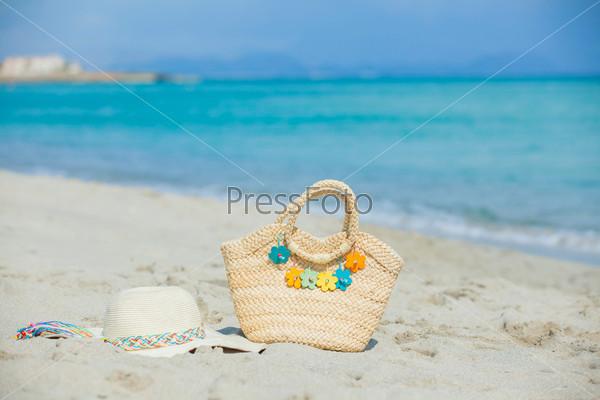 Соломенная шляпа и сумка с цветами на экзотическом песчаном пляже