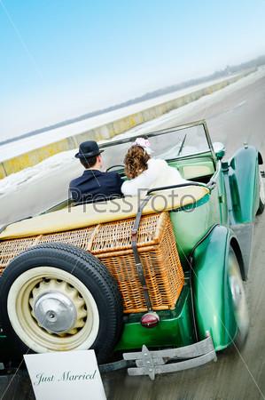 Молодожены в старинном свадебном автомобиле