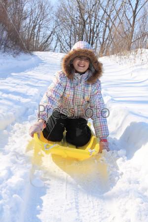 Девушка на санках съезжает с горы
