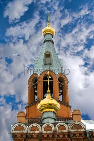 Золотые купола на здание церкви на фоне голубого неба