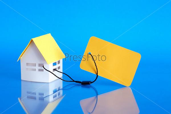 Бумажный дом с желтым ценником на синем фоне