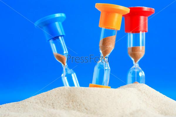 Понятие времени. Цветные песочные часы в песке на синем фоне
