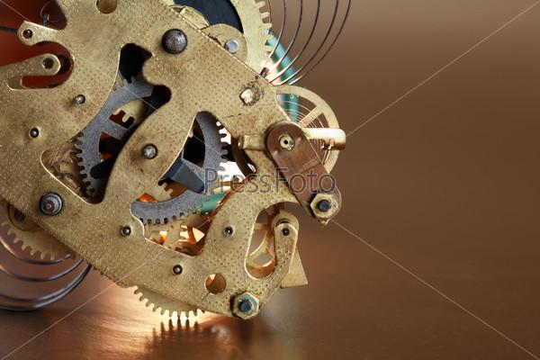 Старый часовой механизм на коричневом фоне крупным планом