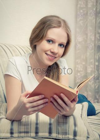 Девушка читает книгу, лежа на диване дома