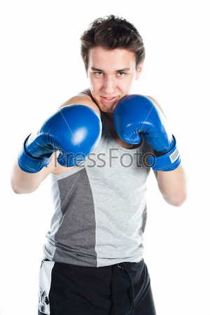 Молодой боксер в серой футболке и синих боксерских перчатках