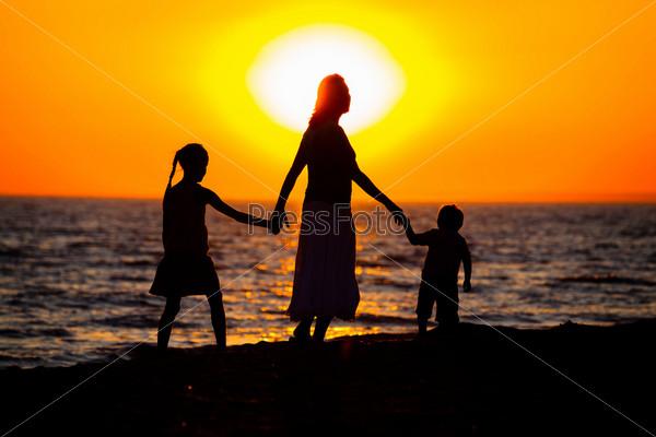 Силуэты матери и детей на пляже на закате