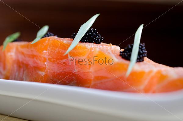 Фотография на тему Ломтики лосося с черной икрой тобико и зеленью