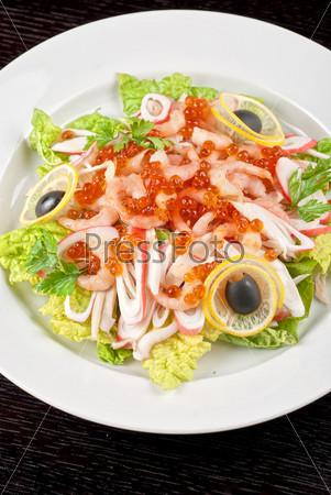 Салат с креветками, икрой, кальмарами, салатом, лимоном и оливками