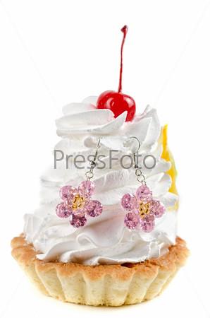 Кекс с кремом и серьгами на белом фоне