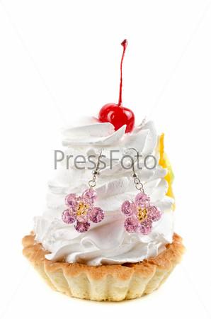 Бижутерия на кексе с кремом на белом фоне