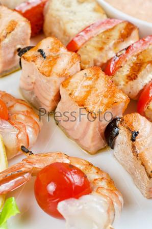 Жареные креветки, перец, помидоры и лосось на бамбуковых палочках