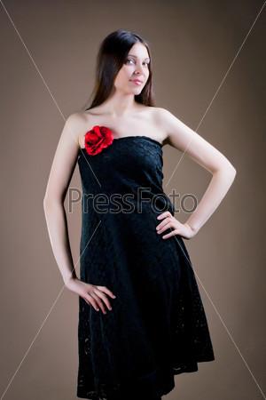 Портрет привлекательной женщины с красным цветком на платье