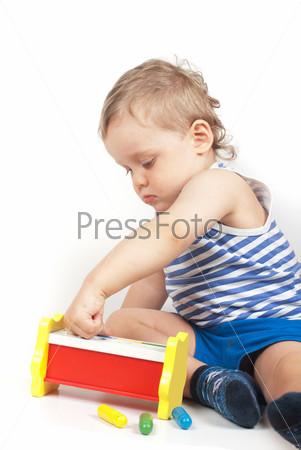 Маленький мальчик с игрушкой на белом фоне