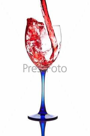 Красное вино, наливаемое в бокал