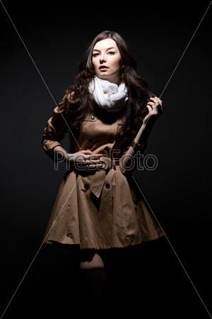Портрет чувственный молодой женщины в коричневом плаще на темном фоне