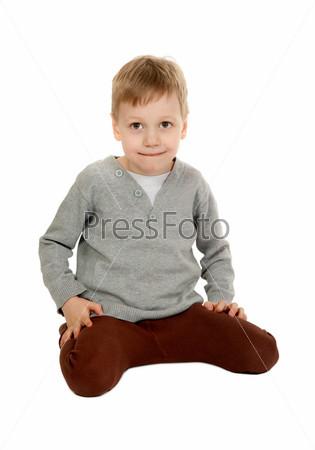 Ребенок сидит в студии на белом фоне