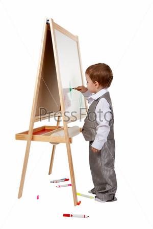 Ребенок рисует на мольберте в студии, изолированный на белом фоне