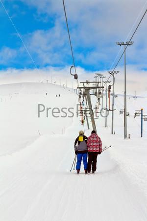 Лыжники поднимаются по горнолыжному склону на подъемнике