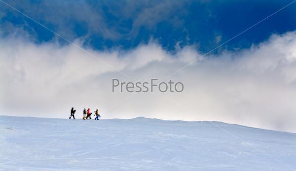 Фотография на тему Четыре сноубордиста идут в гору на фоне неба