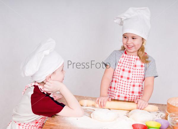Девочка и мальчик говорят и готовят еду