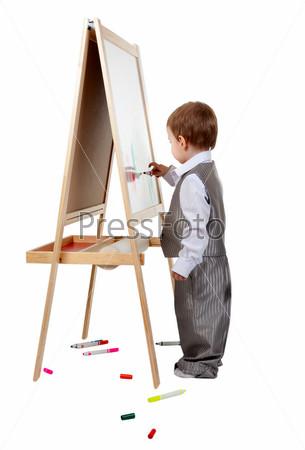 Ребенок рисует на мольберте