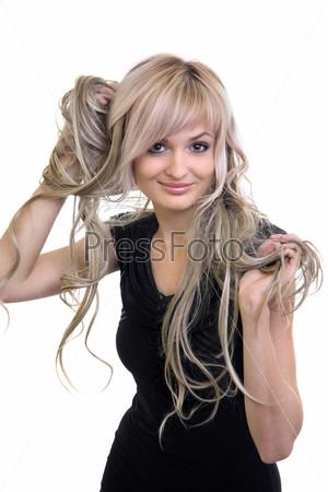 Девушка играет своими белокурыми волосами на белом фоне