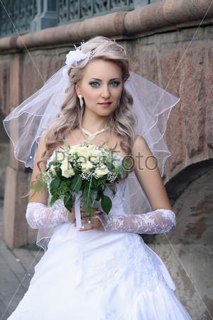 Фотография на тему Невеста со свадебным букетом у каменной стены