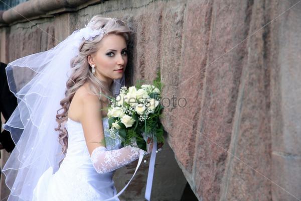 Невеста со свадебным букетом у каменной стены