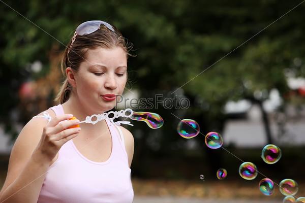 Девушка пускает мыльные пузыри в городском парке