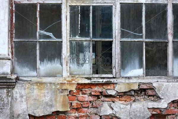Разбитое окно на разрушенной стене