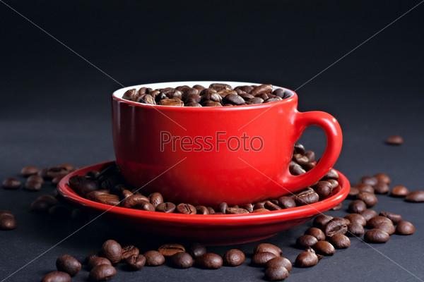 Чашка на блюдце с кофейными зернами на темном фоне