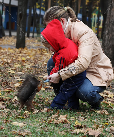Маленький мальчик с мамой кормят белку в парке