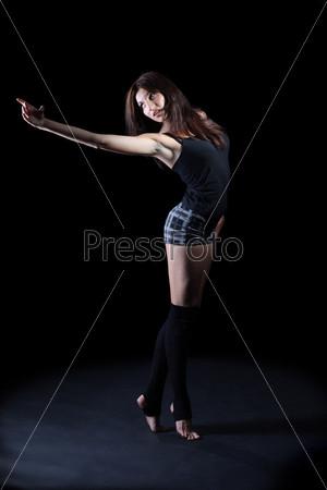 Девушка танцует на темном фоне