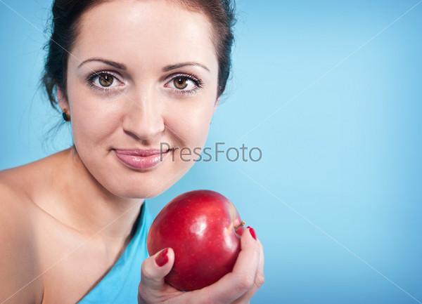 Фотография на тему Улыбающаяся женщина с красным яблоком на голубом фоне