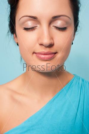 Молодая красивая женщина с закрытыми глазами на голубом фоне