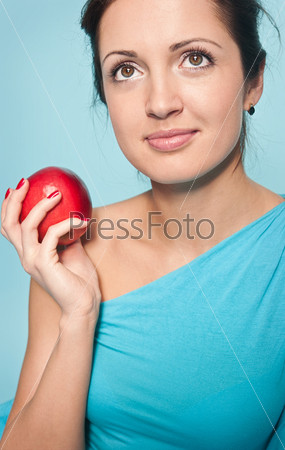 Мечтательная женщина с красным яблоком на голубом фоне