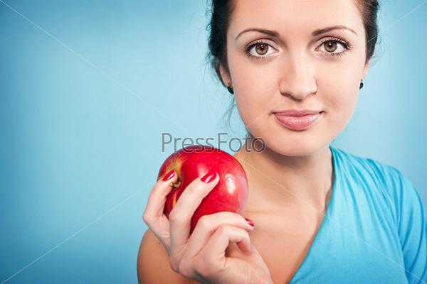 Красивая женщина с красным яблоком на голубом фоне