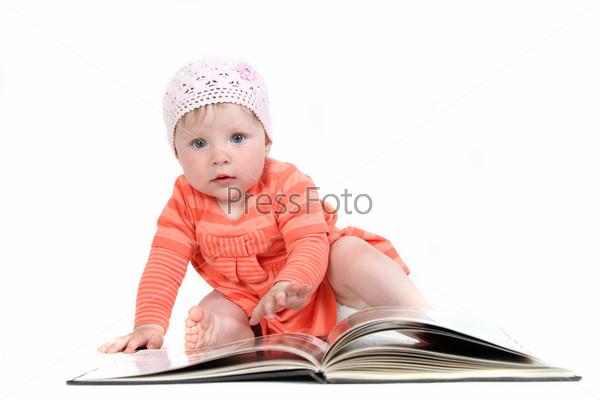 Маленькая девочка листает книгу