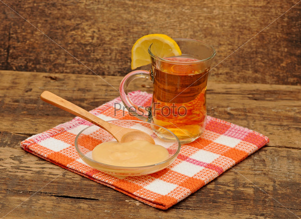 Чай с лимоном и мед на деревянном столе
