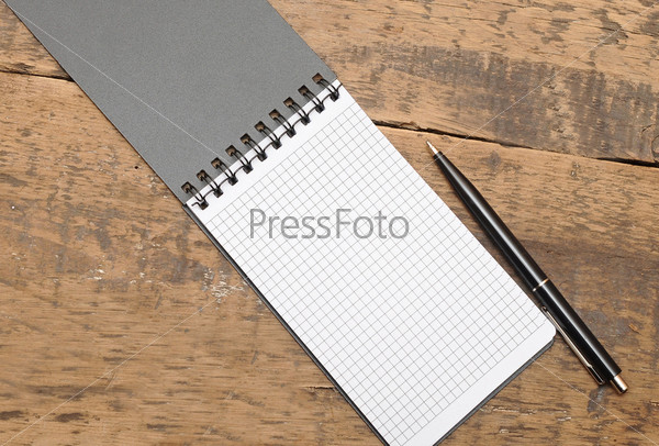 Блокнот с ручкой на деревянном фоне