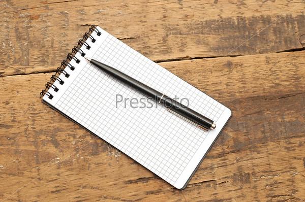 Фотография на тему Блокнот с ручкой на деревянном фоне