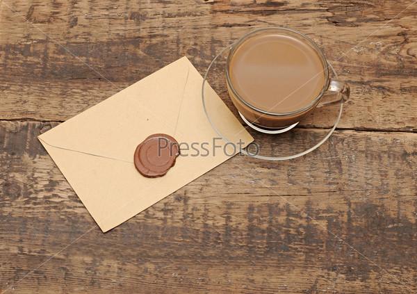 Фотография на тему Конверт с сургучной печатью и чашка кофе на деревянном столе