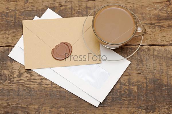 Конверт с сургучной печатью и чашка кофе на деревянном столе