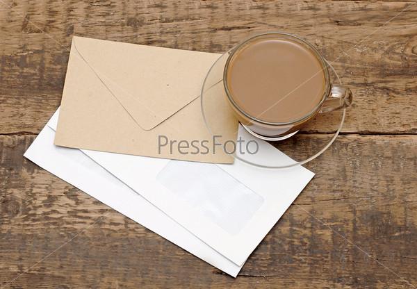 Конверты и чашка кофе на деревянном столе