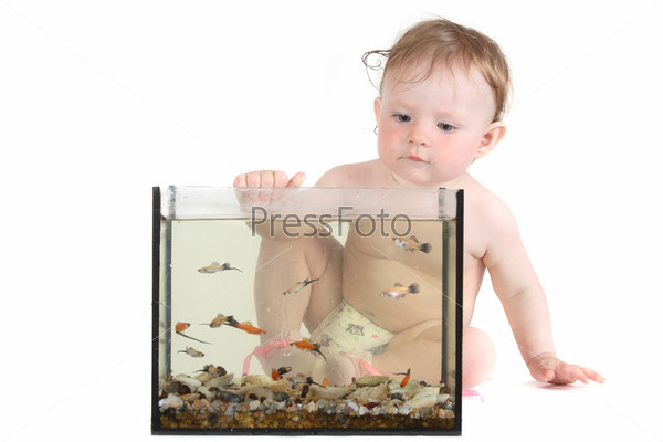 Маленькая девочка играет с аквариумными рыбками