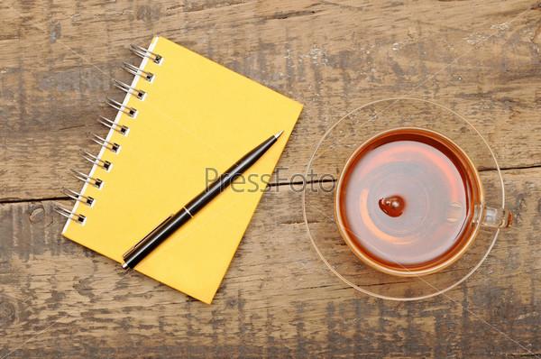Блокнот с ручкой и чашка чая на столе