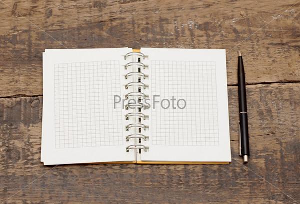 Блокнот с ручкой на деревянном столе