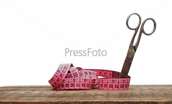 Ножницы и сантиметровая лента на столе