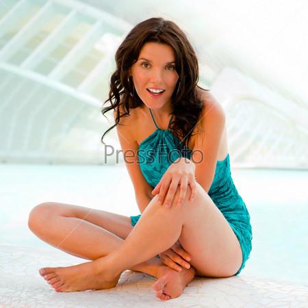 Девушка отдыхает возле бассейна на современном тропическом курорте со стильным зданием на заднем плане