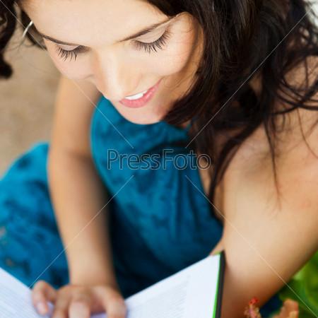 Расслабленная женщина читает книгу в парке